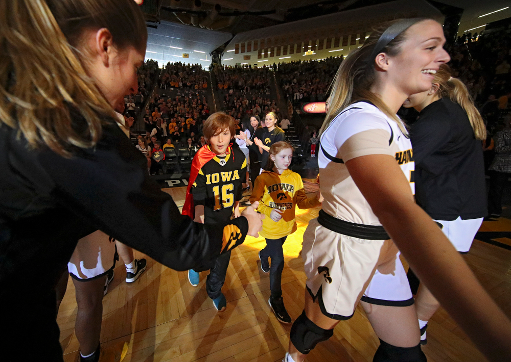Iowa Hawkeyes guard Makenzie Meyer (3) is introduced with two Go Red for Women Movement Heart Champions before the start of their game at Carver-Hawkeye Arena in Iowa City on Sunday, January 26, 2020. (Stephen Mally/hawkeyesports.com)