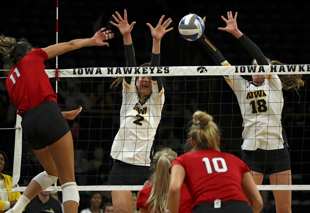 Iowa's Courtney Buzzerio (2) and Hannah Clayton (18) try for a block during the first set of their match against Nebraska at Carver-Hawkeye Arena in Iowa City on Saturday, Nov 9, 2019. (Stephen Mally/hawkeyesports.com)
