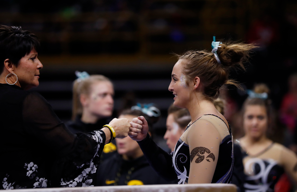 Iowa assistant coach Jennifer Green and Bre Fitzke as she competes on the beam against the Nebraska Cornhuskers