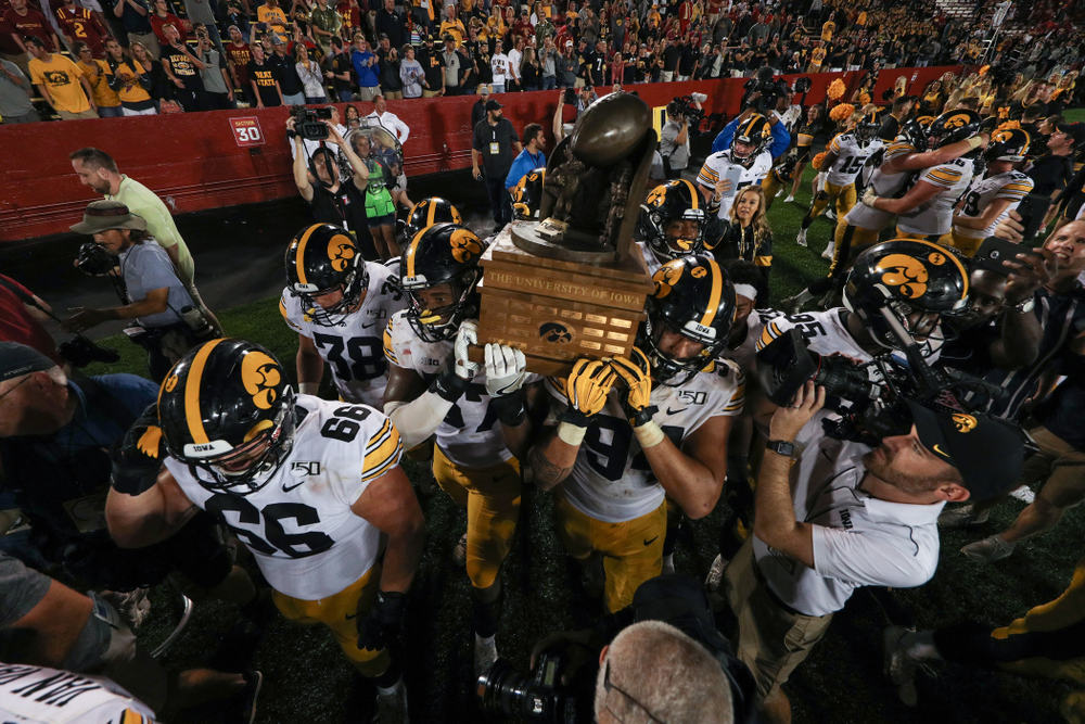 Iowa Hawkeyes defensive end Chauncey Golston (57) and defensive end A.J. Epenesa (94) carry the Cy-Hawk trophy off the field following their game against the Iowa State Cyclones Saturday, September 14, 2019 in Ames, Iowa. (Brian Ray/hawkeyesports.com)
