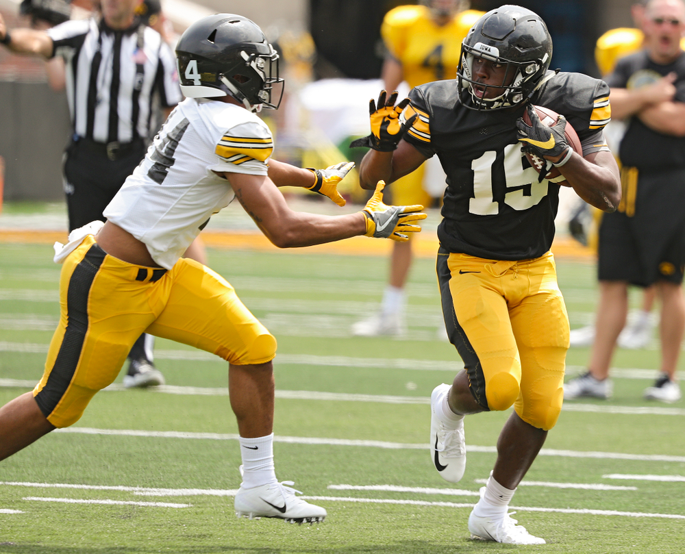 Iowa Hawkeyes running back Tyler Goodson (15) tries to hold off defensive back Daraun McKinney (14) during Fall Camp Practice No. 8 at Kids Day at Kinnick Stadium in Iowa City on Saturday, Aug 10, 2019. (Stephen Mally/hawkeyesports.com)