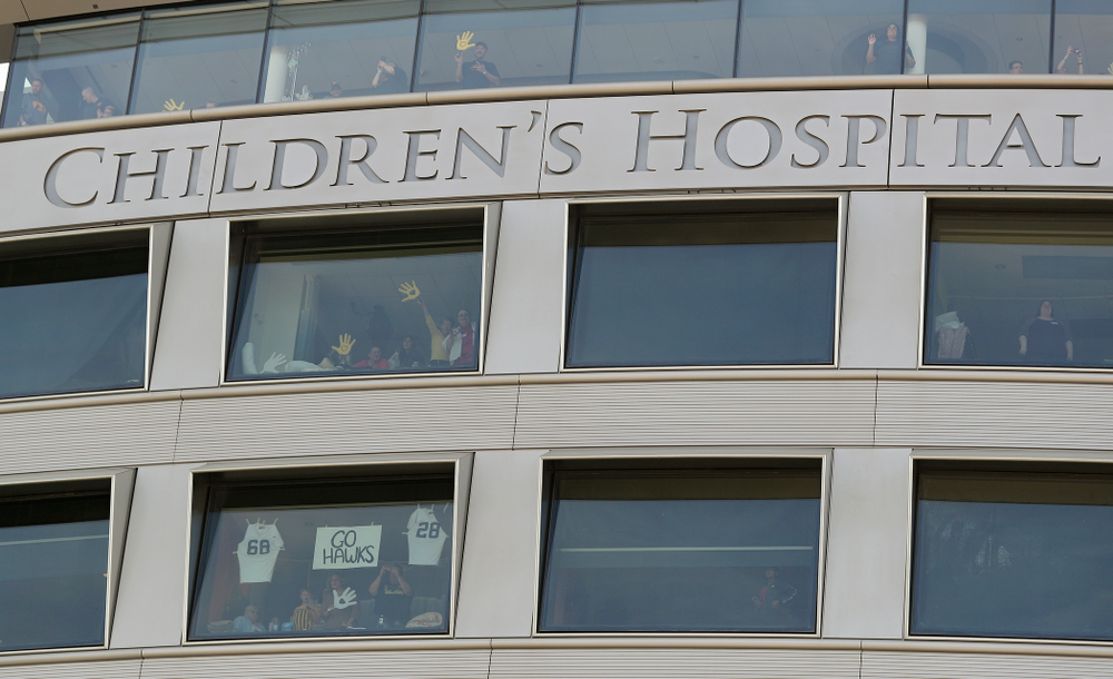 """People look on from the University of Iowa Stead Family Children's Hospital as the Pat Green performs """"Wave on Wave"""" during the second quarter of their Big Ten Conference football game at Kinnick Stadium in Iowa City on Saturday, Sep 7, 2019. (Stephen Mally/hawkeyesports.com)"""