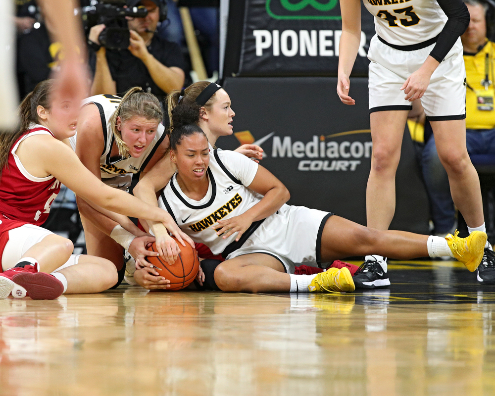 Iowa Hawkeyes forward Monika Czinano (25) and guard Alexis Sevillian (5) keep their hands on a held ball during the third quarter of their game at Carver-Hawkeye Arena in Iowa City on Sunday, January 12, 2020. (Stephen Mally/hawkeyesports.com)