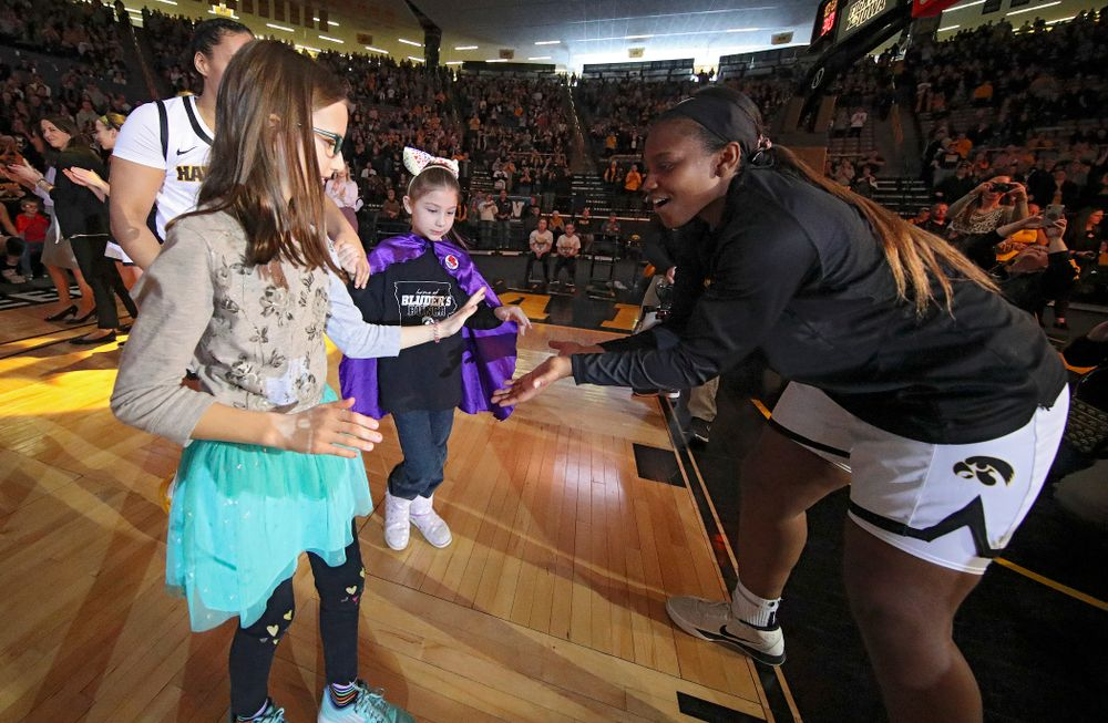 Iowa Hawkeyes guard Alexis Sevillian (right) gets a high-five from two Go Red for Women Movement Heart Champions before the start of their game at Carver-Hawkeye Arena in Iowa City on Sunday, January 26, 2020. (Stephen Mally/hawkeyesports.com)