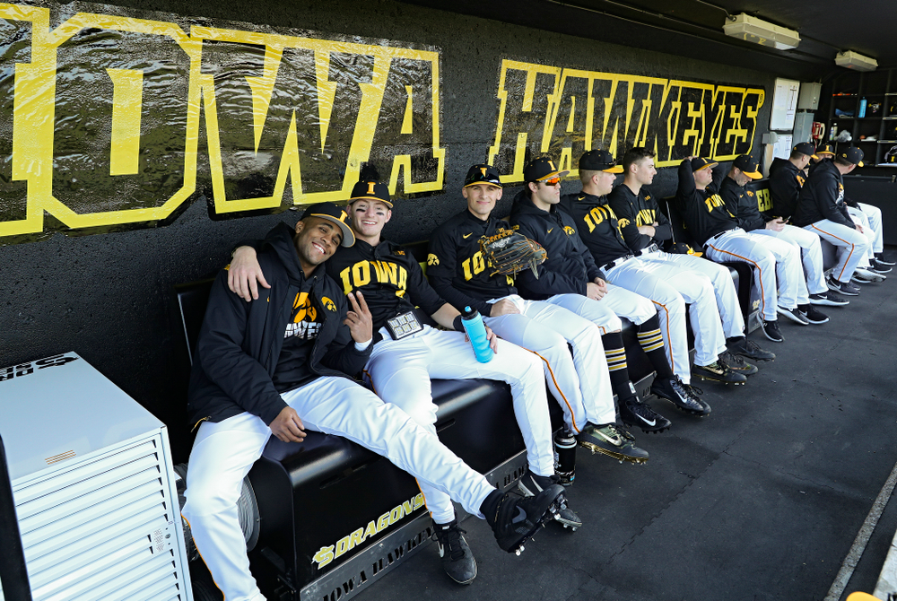 Iowa Hawkeyes players sit on their new Dragon Seats heated benches in the dugout before their game at Duane Banks Field in Iowa City on Tuesday, March 3, 2020. (Stephen Mally/hawkeyesports.com)