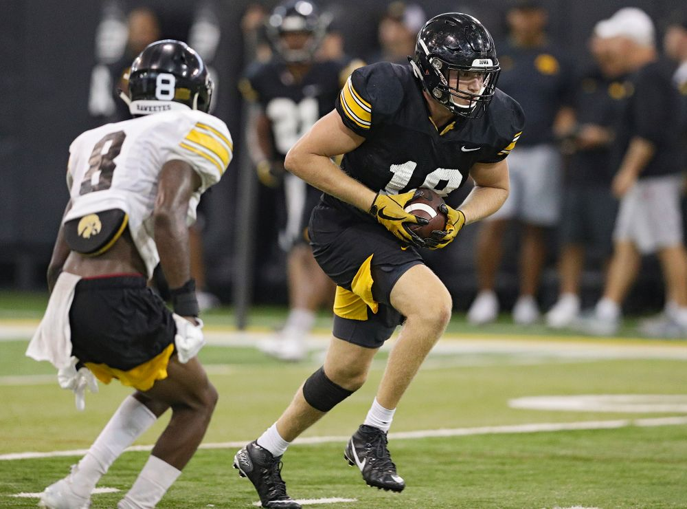 Iowa Hawkeyes tight end Drew Cook (18) pulls in a pass as defensive back Matt Hankins (8) closes in during Fall Camp Practice No. 9 at the Hansen Football Performance Center in Iowa City on Monday, Aug 12, 2019. (Stephen Mally/hawkeyesports.com)