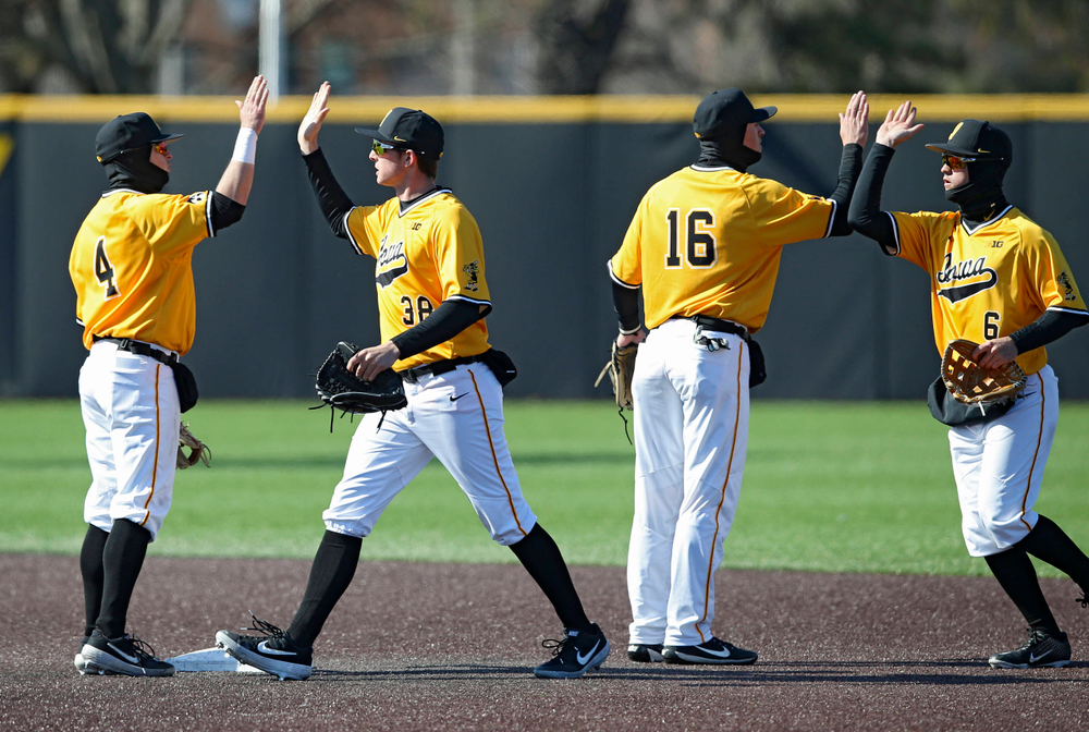 Iowa Hawkeyes second baseman Mitchell Boe (4), left fielder Trenton Wallace (38), shortstop Tanner Wetrich (16), and center fielder Justin Jenkins (6) celebrate after winning their game against Illinois at Duane Banks Field in Iowa City on Sunday, Mar. 31, 2019. (Stephen Mally/hawkeyesports.com)