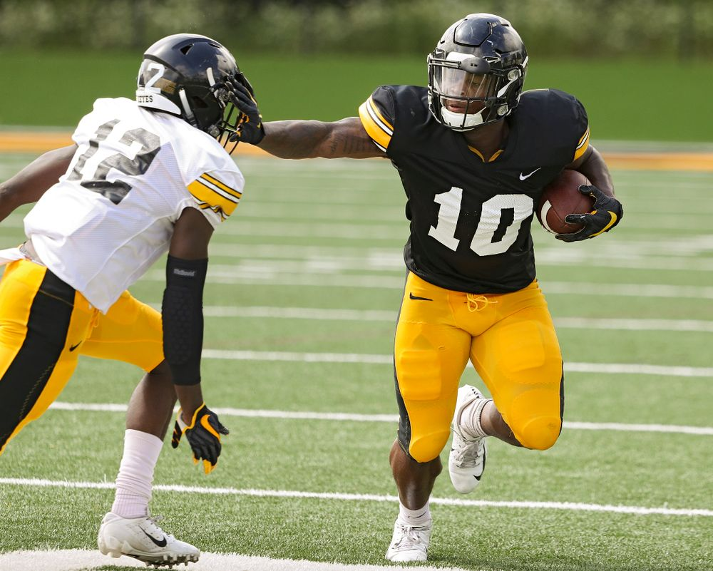 Iowa Hawkeyes running back Mekhi Sargent (10) tries to hold off defensive back D.J. Johnson (12) during Fall Camp Practice No. 10 at the Hansen Football Performance Center in Iowa City on Tuesday, Aug 13, 2019. (Stephen Mally/hawkeyesports.com)