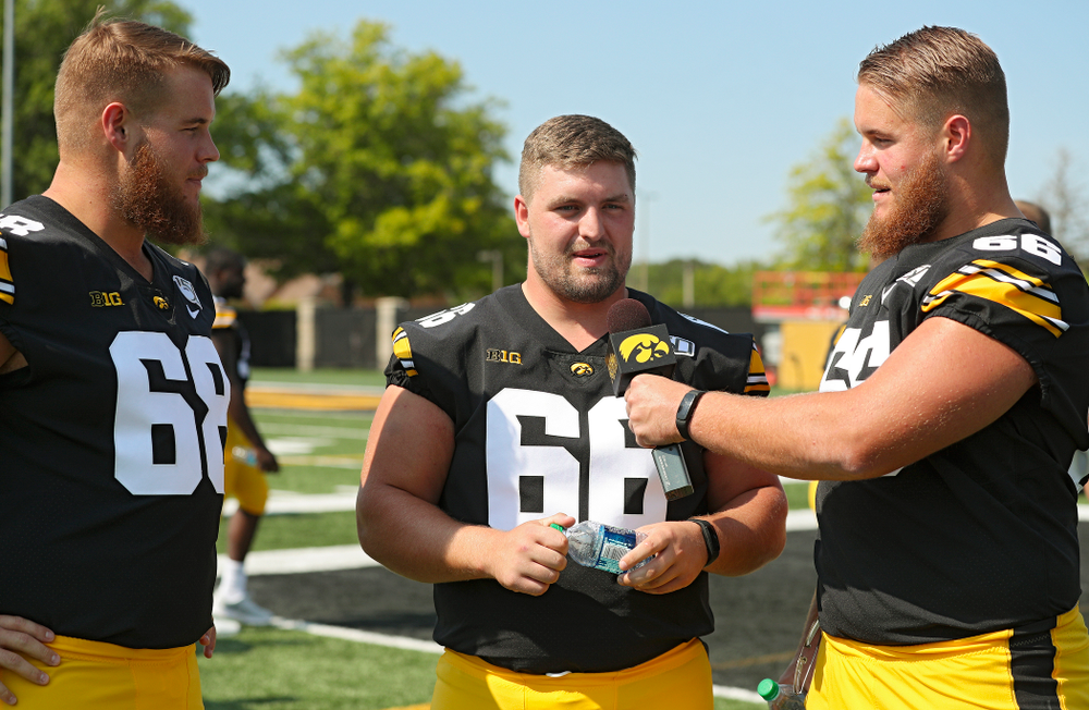 Iowa Hawkeyes offensive lineman Levi Paulsen (right) interviews defensive lineman Dalles Jacobus (center) as offensive lineman Landan Paulsen (68) looks on during Iowa Football Media Day at the Hansen Football Performance Center in Iowa City on Friday, Aug 9, 2019. (Stephen Mally/hawkeyesports.com)