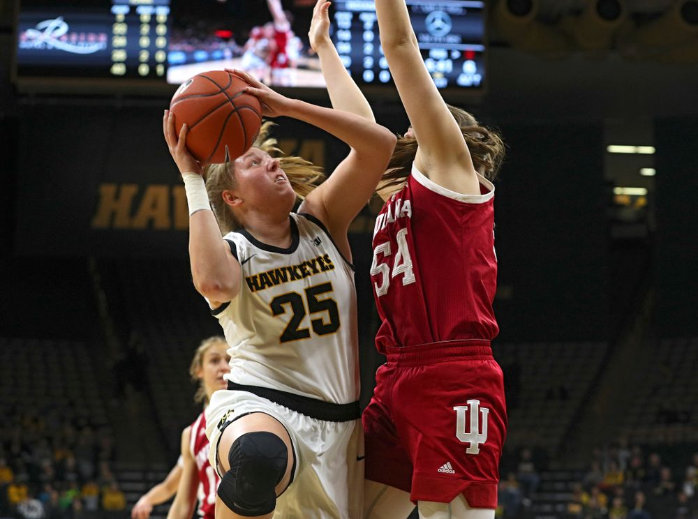 Iowa Hawkeyes forward Monika Czinano (25) scores a basket around the arms of Indiana Hoosiers forward Mackenzie Holmes (54) during the first quarter of their game at Carver-Hawkeye Arena in Iowa City on Sunday, January 12, 2020. (Stephen Mally/hawkeyesports.com)