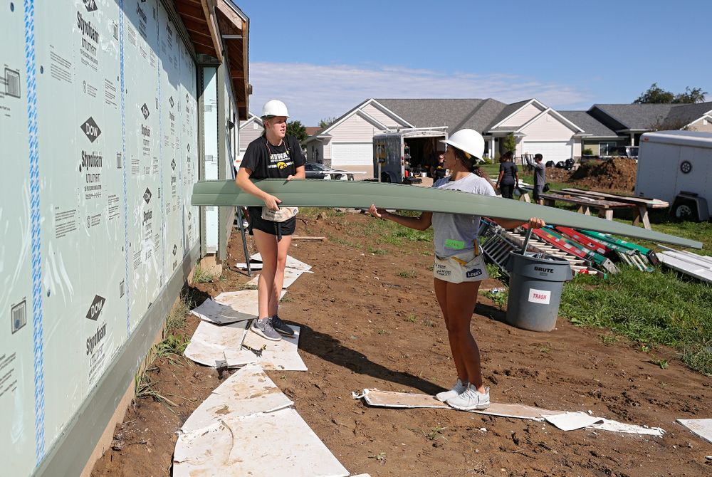 Iowa's Monika Czinano (from left) and Gabbie Marshall carry a piece of siding as they work on a Habitat for Humanity Women Build project in Iowa City on Wednesday, Sep 25, 2019. (Stephen Mally/hawkeyesports.com)