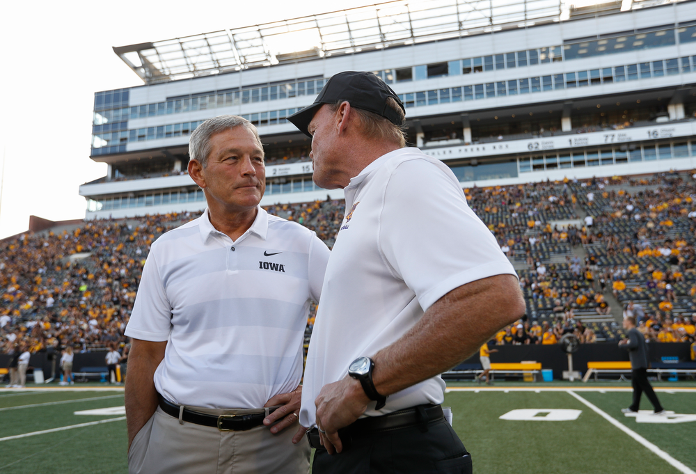 Iowa Hawkeyes head coach Kirk Ferentz and Northern Iowa head coach Mark Farley talk before a game against Northern Iowa at Kinnick Stadium on September 15, 2018. (Tork Mason/hawkeyesports.com)