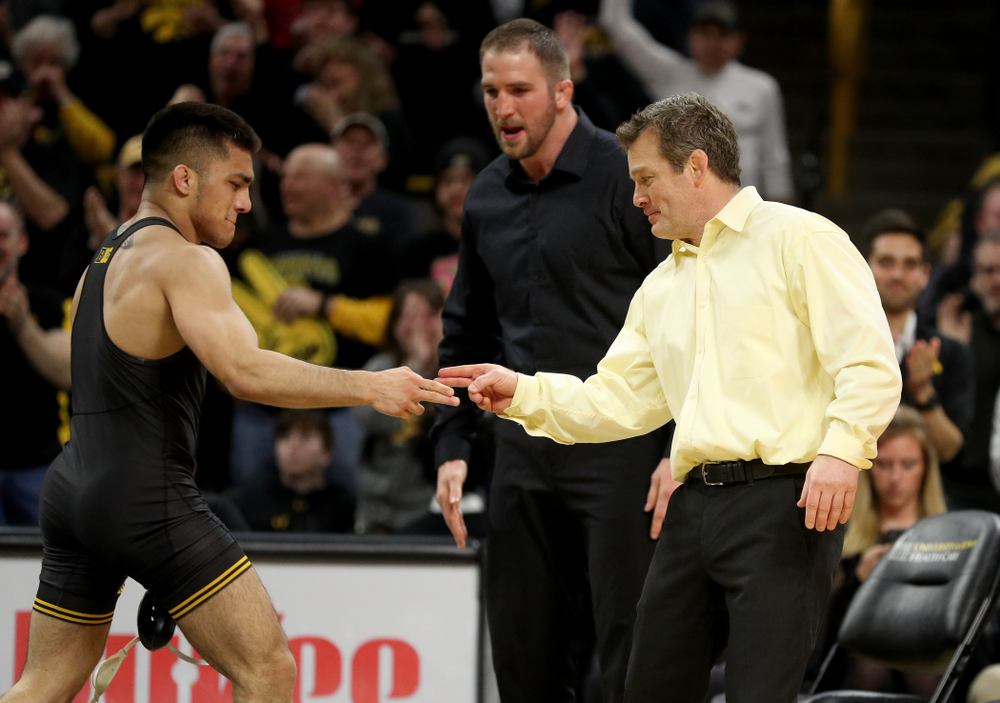 Iowa's Pat Lugo and head coach Tom Brands after defeating Oklahoma State's Boo Luwallen at 149 pounds Sunday, February 23, 2020 at Carver-Hawkeye Arena. Lugo won the match by fall. (Brian Ray/hawkeyesports.com)