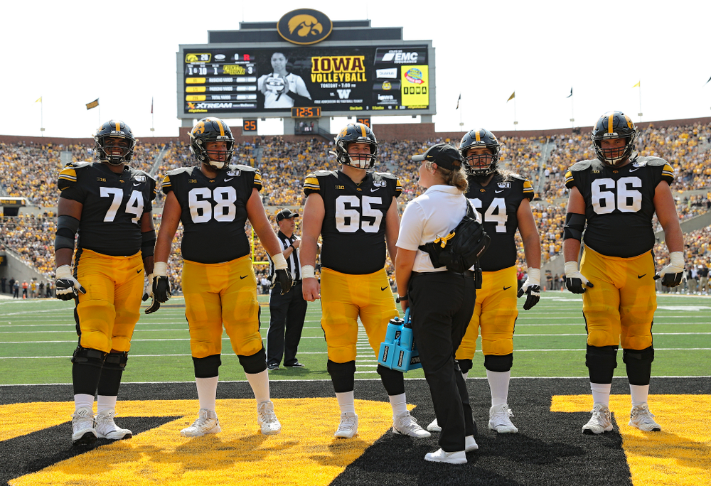 Iowa Hawkeyes offensive lineman Tristan Wirfs (74), offensive lineman Landan Paulsen (68), offensive lineman Tyler Linderbaum (65), offensive lineman Kyler Schott (64), and offensive lineman Levi Paulsen (66) on the field during a TV timeout during the third quarter of their Big Ten Conference football game at Kinnick Stadium in Iowa City on Saturday, Sep 7, 2019. (Stephen Mally/hawkeyesports.com)