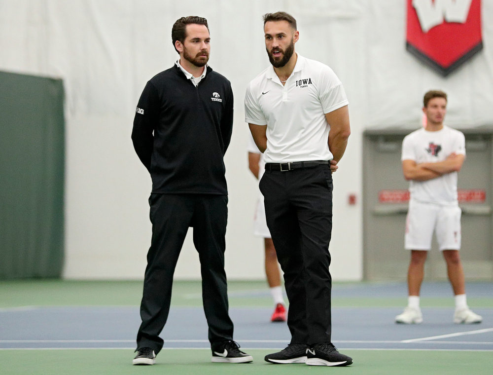 Iowa head coach Ross Wilson and assistant coach Lloyd Bruce-Burgess talk during their match at the Hawkeye Tennis and Recreation Complex in Iowa City on Thursday, January 16, 2020. (Stephen Mally/hawkeyesports.com)