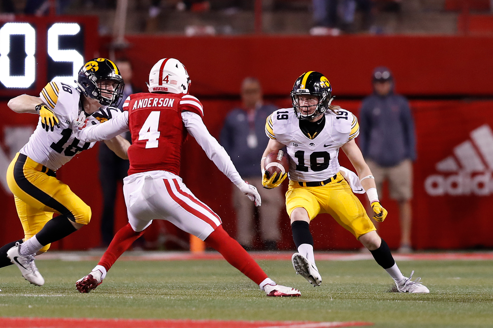Iowa Hawkeyes wide receiver Max Cooper (19) and defensive back John Milani (18)