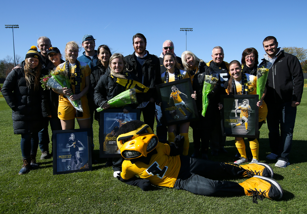 Senior members of the Iowa Hawkeyes soccer team pose for a photo with their families and Herky the Hawk during Senior Day ceremonies before a game against Northwestern at the Iowa Soccer Complex on October 21, 2018. (Tork Mason/hawkeyesports.com)
