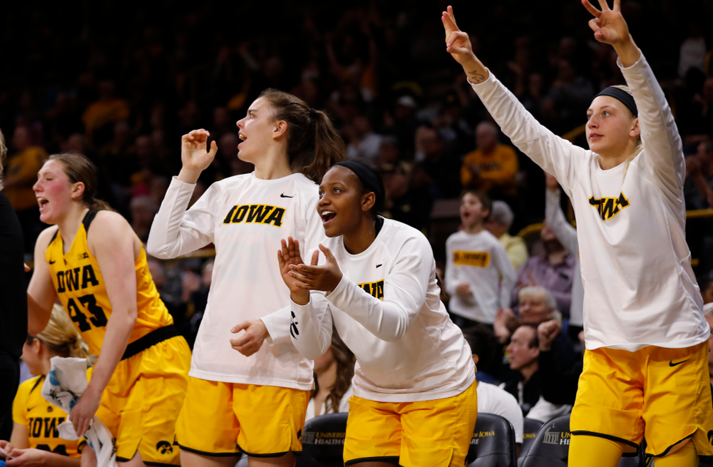 Iowa Hawkeyes guard Zion Sanders (24), forward Carly Mohns (34), and forward/center Paula Valino Ramos (31)