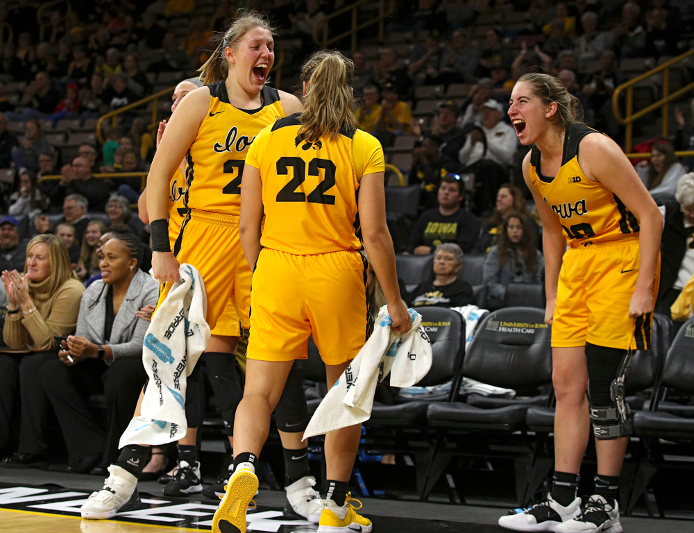 Iowa forward/center Monika Czinano (25), guard Kathleen Doyle (22), and guard Kate Martin (20) celebrate on the bench during the fourth quarter of their game against Winona State at Carver-Hawkeye Arena in Iowa City on Sunday, Nov 3, 2019. (Stephen Mally/hawkeyesports.com)
