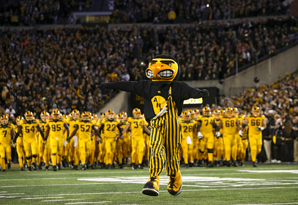 Herky leads the Hawkeyes as they swarm to take the field before their game at Kinnick Stadium in Iowa City on Saturday, Oct 12, 2019. (Stephen Mally/hawkeyesports.com)