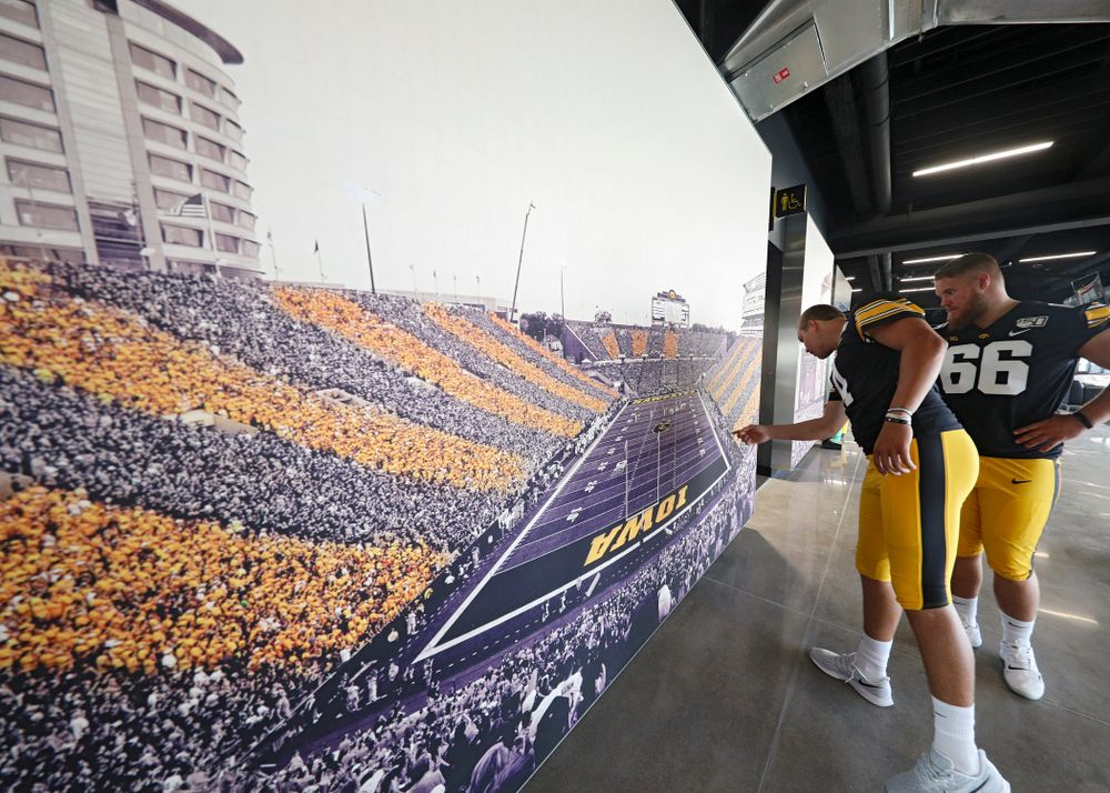 Iowa Hawkeyes quarterback Nate Stanley (4) and offensive lineman Levi Paulsen (66) look at a picture in the new Ted Pacha Family Club at Kinnick Stadium in Iowa City on Friday, Aug 9, 2019. (Stephen Mally/hawkeyesports.com)