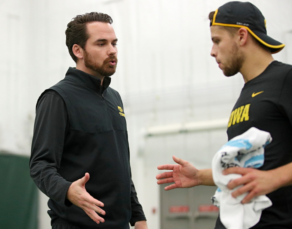 Iowa's Mellecker Family head men's tennis coach Ross Wilson (from left) talks with Will Davies serves during his match against Marquette at the Hawkeye Tennis and Recreation Complex in Iowa City on Saturday, January 25, 2020. (Stephen Mally/hawkeyesports.com)