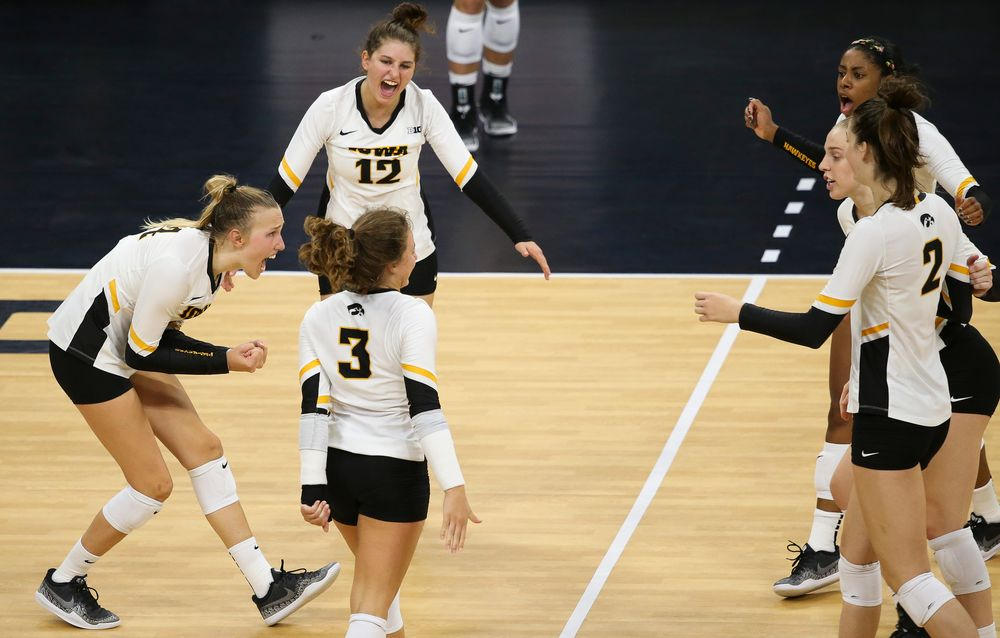 Iowa Hawkeyes outside hitter Cali Hoye (14), Iowa Hawkeyes defensive specialist Emily Bushman (12)