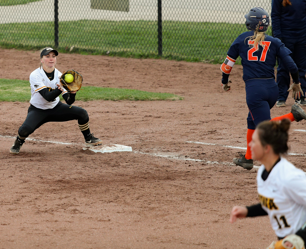 Iowa second baseman Aralee Bogar (2) fields a throw from third baseman Mallory Kilian (11) at first base for an out on a bunt play during the fifth inning of their game against Illinois at Pearl Field in Iowa City on Friday, Apr. 12, 2019. (Stephen Mally/hawkeyesports.com)