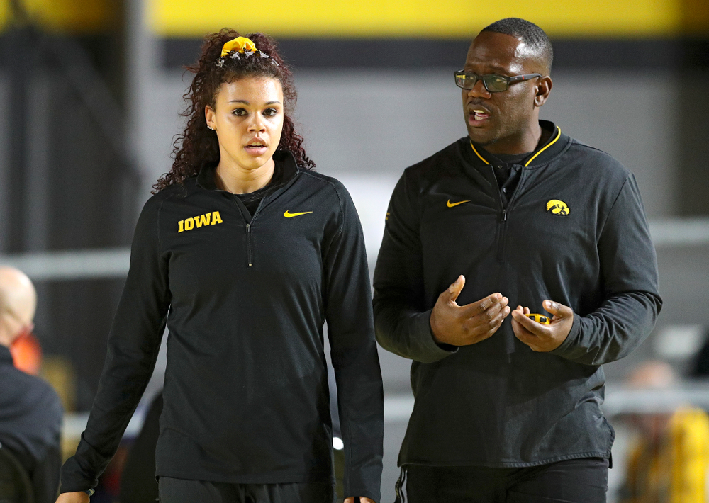 Iowa's Dallyssa Huggins (from left) talks with associate head coach Clive Roberts during the Larry Wieczorek Invitational at the Recreation Building in Iowa City on Friday, January 17, 2020. (Stephen Mally/hawkeyesports.com)