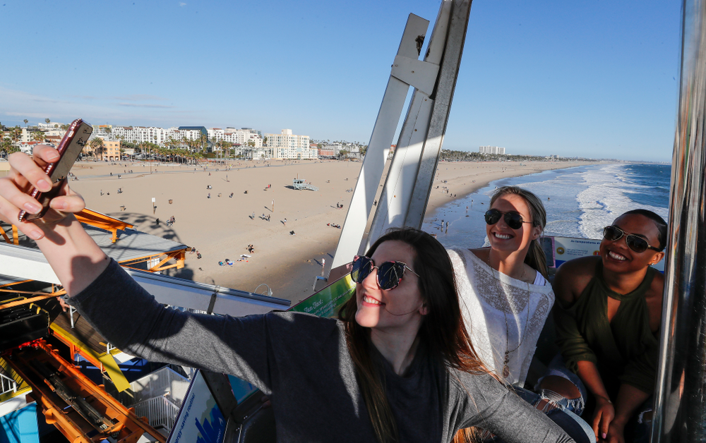 Iowa Hawkeyes forward Megan Gustafson (10) takes a selfie with guard Makenzie Meyer (3), guard Alexis Sevillian (5) and guard Tania Davis (11) as they ride the ferris wheel in Pacific Park on the Santa Monica Pier Thursday, March 15, 2018 in Santa Monica. (Brian Ray/hawkeyesports.com)