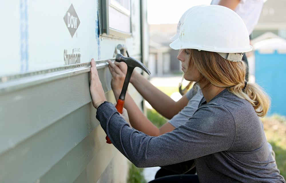 Iowa's Makenzie Meyer hammers in a nail on a piece of siding as they work on a Habitat for Humanity Women Build project in Iowa City on Wednesday, Sep 25, 2019. (Stephen Mally/hawkeyesports.com)