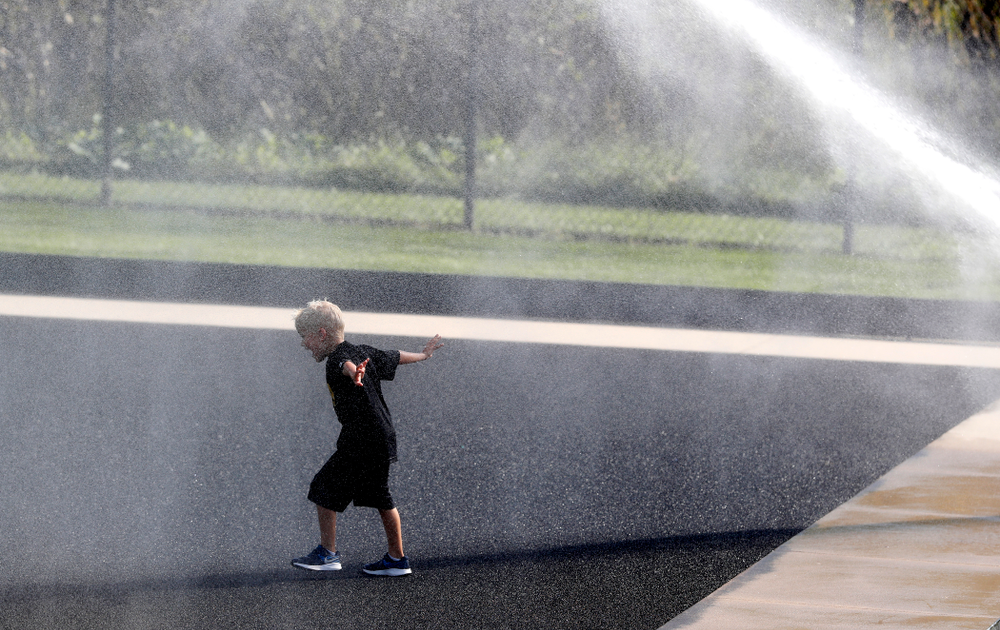 A young boy plays in the sprinklers as the field is watered at half time of the Iowa Hawkeyes game against the Penn Quakers Friday, September 14, 2018 at Grant Field. (Brian Ray/hawkeyesports.com)