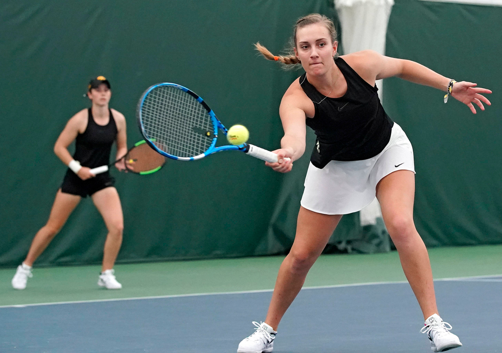 Iowa's Ashleigh Jacobs (right) returns a shot as Elise van Heuvelen Treadwell (left) looks on during their doubles match against Indiana at the Hawkeye Tennis and Recreation Complex in Iowa City on Sunday, Mar. 31, 2019. (Stephen Mally/hawkeyesports.com)