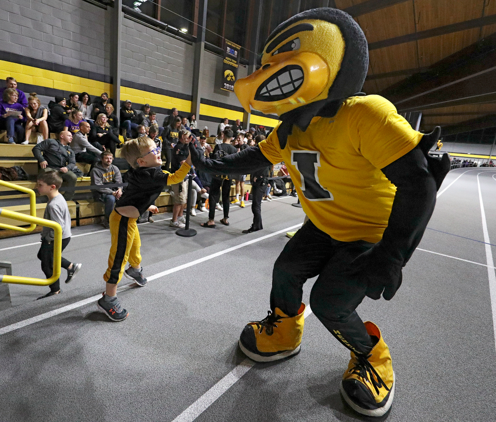 Herky gets a high-five from a young fan before the Herky Kid's Race during the Jimmy Grant Invitational at the Recreation Building in Iowa City on Saturday, December 14, 2019. (Stephen Mally/hawkeyesports.com)