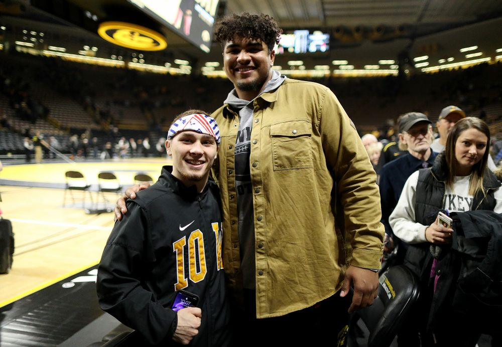 Iowa's Spencer Lee takes a photo with Hawkeye Football's Tristan Wirfs following their win over the Nebraska's Cornhuskers Saturday, January 18, 2020 at Carver-Hawkeye Arena. (Brian Ray/hawkeyesports.com)