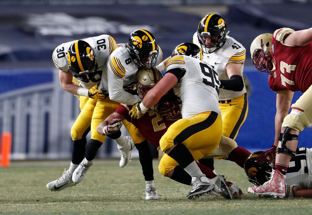 Iowa Hawkeyes defensive back Matt Hankins (8) and defensive lineman Cedrick Lattimore (95)