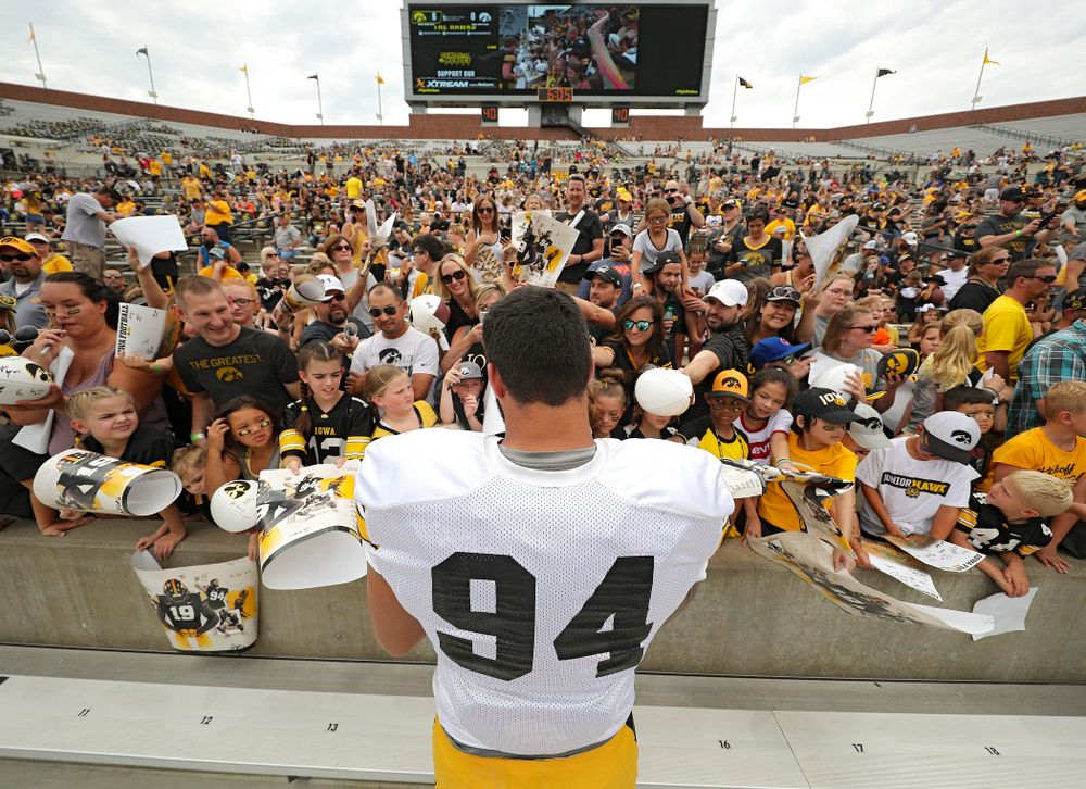 Iowa Hawkeyes defensive end A.J. Epenesa (94) signs autographs during Kids Day at Kinnick Stadium in Iowa City on Saturday, Aug 10, 2019. (Stephen Mally/hawkeyesports.com)