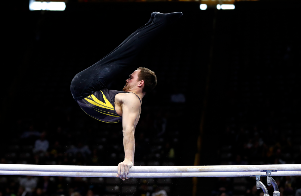 Dylan Ellsworth competes on the bars against Illinois