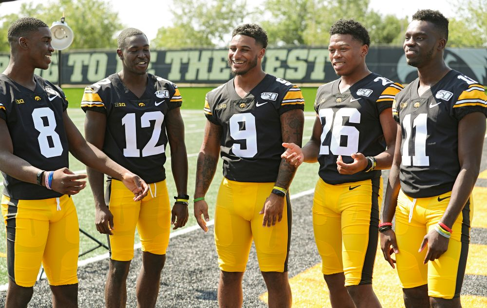 Iowa Hawkeyes defensive back Matt Hankins (8), defensive back D.J. Johnson (12), defensive back Geno Stone (9), defensive back Kaevon Merriweather (26), and defensive back Michael Ojemudia (11) pose for a picture during Iowa Football Media Day at the Hansen Football Performance Center in Iowa City on Friday, Aug 9, 2019. (Stephen Mally/hawkeyesports.com)