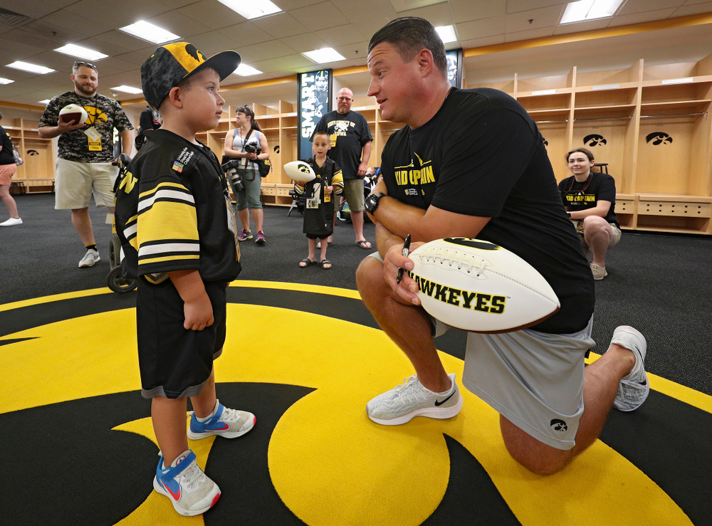 Kid Captain Jeg Weets (from left) talks with Iowa Hawkeyes offensive coordinator Brian Ferentz during Kids Day at Kinnick Stadium in Iowa City on Saturday, Aug 10, 2019. (Stephen Mally/hawkeyesports.com)