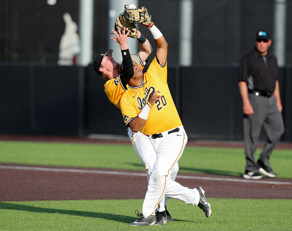 Iowa Hawkeyes second baseman Brendan Sher (2) makes contact with first baseman Izaya Fullard (20) as Fullard pulls in a pop up for an out during the sixth inning of their game against Northern Illinois at Duane Banks Field in Iowa City on Tuesday, Apr. 16, 2019. (Stephen Mally/hawkeyesports.com)