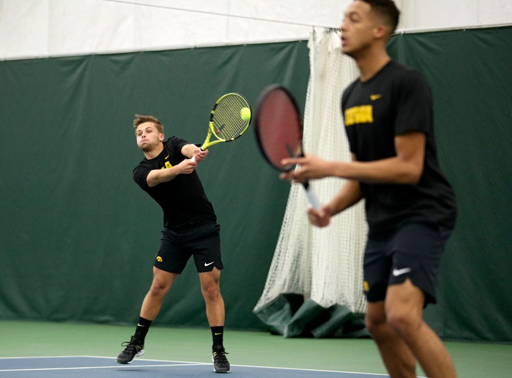 Iowa's Will Davies (from left) returns a shot as Oliver Okonkwo looks on during their doubles match at the Hawkeye Tennis and Recreation Complex in Iowa City on Friday, February 14, 2020. (Stephen Mally/hawkeyesports.com)