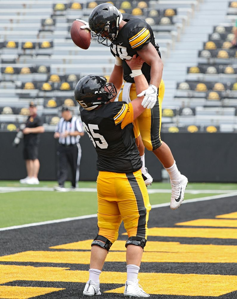Iowa Hawkeyes offensive lineman Tyler Linderbaum (65) holds up running back Toren Young (28) after Young scored a touchdown during Fall Camp Practice No. 8 at Kids Day at Kinnick Stadium in Iowa City on Saturday, Aug 10, 2019. (Stephen Mally/hawkeyesports.com)