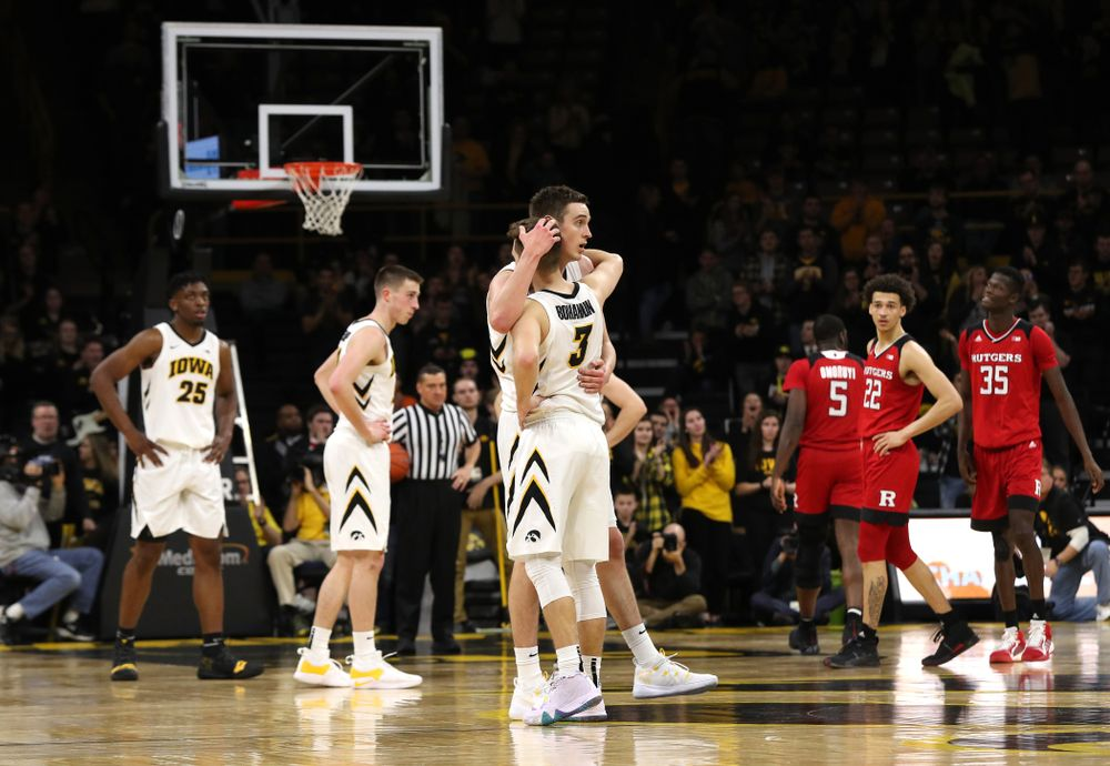 Iowa Hawkeyes forward Nicholas Baer (51) hugs guard Jordan Bohannon (3) as he leaves the court for the final time against the Rutgers Scarlet Knights  Saturday, March 2, 2019 at Carver-Hawkeye Arena. (Brian Ray/hawkeyesports.com)