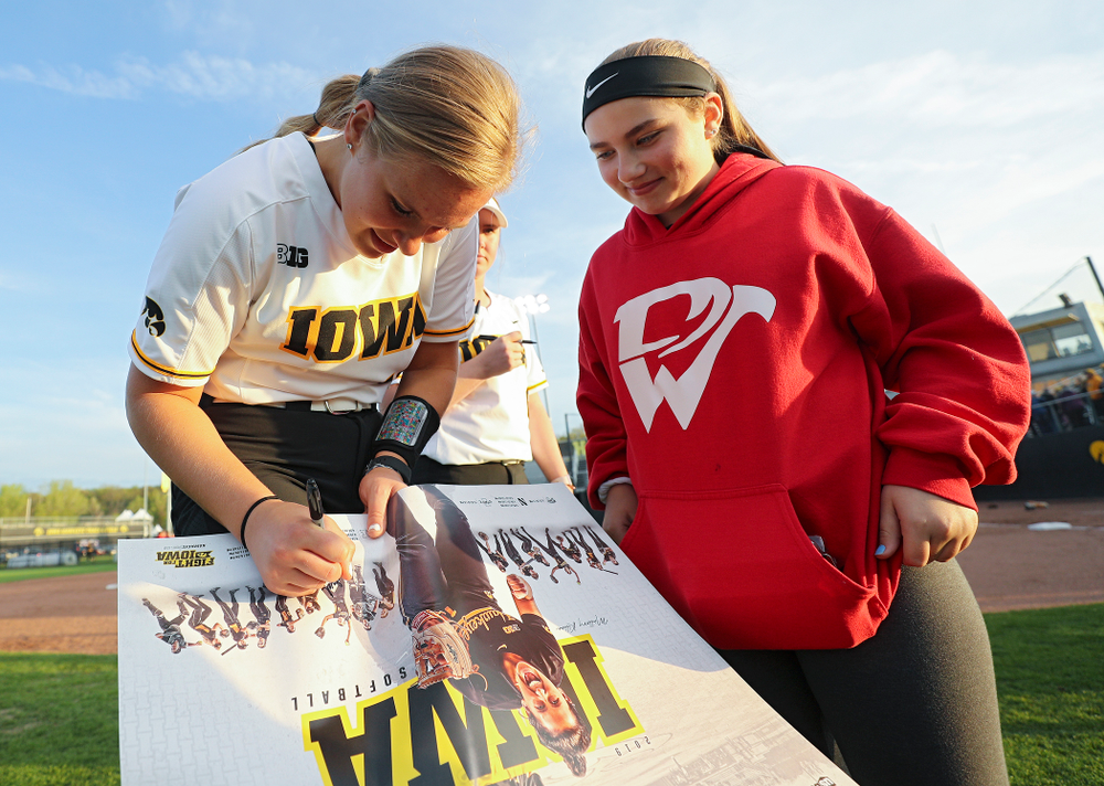 Iowa's Sarah Lehman (16) signs a poster for a fan after winning their game against Ohio State at Pearl Field in Iowa City on Friday, May. 3, 2019. (Stephen Mally/hawkeyesports.com)