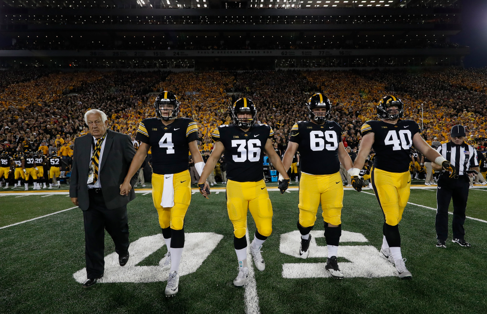 Honorary Captain Tom Moore along with captains quarterback Nate Stanley (4), fullback Brady Ross (36), offensive lineman Keegan Render (69), and defensive end Parker Hesse (40) before their game against the Wisconsin Badgers Saturday, September 22, 2018 at Kinnick Stadium. (Brian Ray/hawkeyesports.com)
