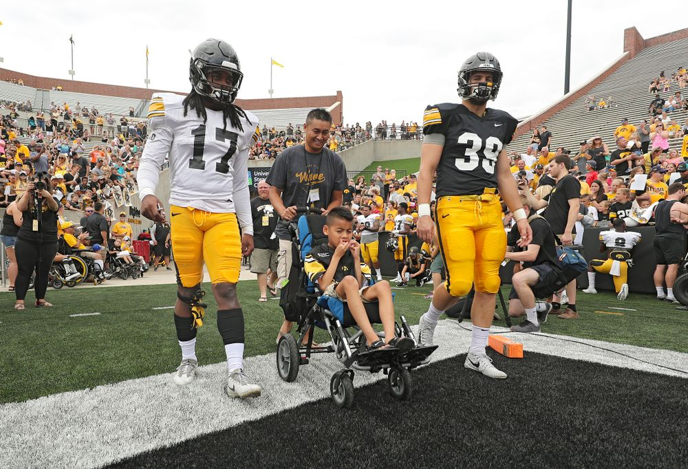 Iowa Hawkeyes defensive back Devonte Young (17) and tight end Nate Wieting (39) swarm with Kid Captain Enzo Thongsoum during Kids Day at Kinnick Stadium in Iowa City on Saturday, Aug 10, 2019. (Stephen Mally/hawkeyesports.com)