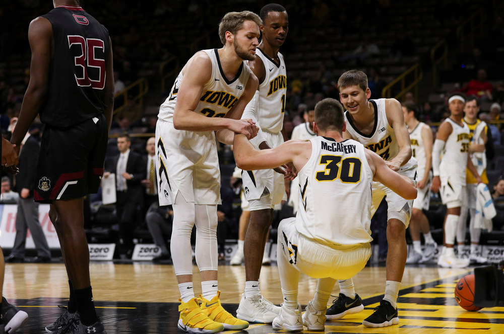 Iowa Hawkeyes forward Riley Till (20) and Iowa Hawkeyes guard Austin Ash (13) pick up Iowa Hawkeyes guard Connor McCaffery (30) after McCaffery was fouled during a game against Guilford College at Carver-Hawkeye Arena on November 4, 2018. (Tork Mason/hawkeyesports.com)