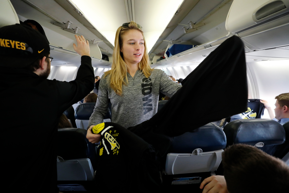 Iowa Hawkeyes guard Makenzie Meyer (3) hands out t-shirts to the pep band and spirit squad to thank them as they travel to Los Angeles for the first round of the 2018 NCAA Tournament Thursday, March 15, 2018 at the Eastern Iowa Airport. (Brian Ray/hawkeyesports.com)