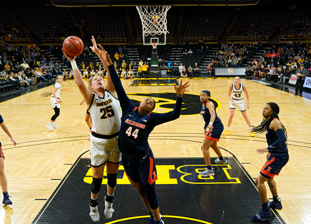 Iowa Hawkeyes forward Monika Czinano (25) scores a basket over the hand of Illinois Fighting Illini forward Kennedi Myles (44) during the third quarter of their game at Carver-Hawkeye Arena in Iowa City on Tuesday, December 31, 2019. (Stephen Mally/hawkeyesports.com)